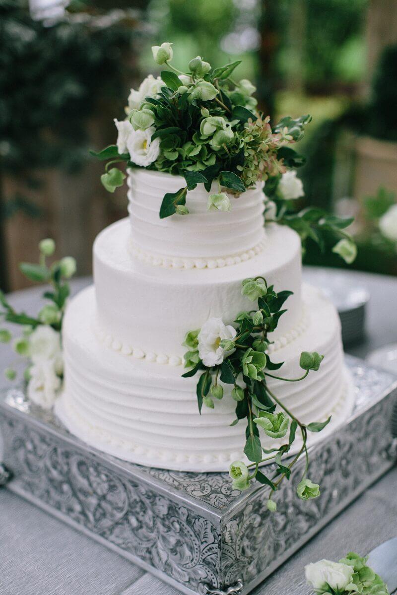 weiße Hochzeitstorte mit grüner Blumendeko