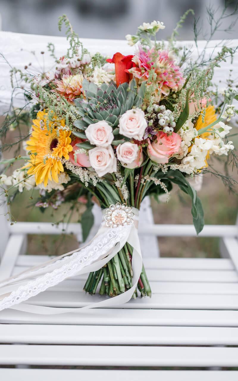 Rustikaler Brautstrauß mit Spitzenbändern und Brosche