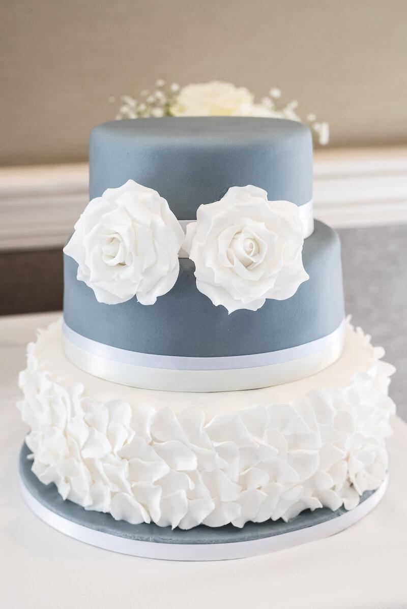Hochzeitstorte in Blau mit weißen Rüschen
