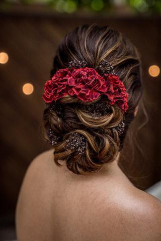 Brautfrisur hochgesteckt mit roten Haarblumen